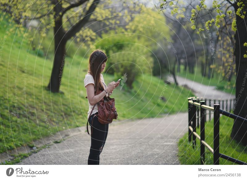 Young woman with long brown hair checking her mobile outdoors Woman Human being Nature Vacation & Travel Youth (Young adults) Summer Plant Beautiful Green Tree