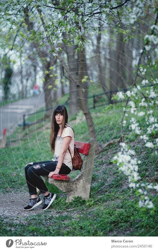 Young woman sitting on a bench in a park in serene pose Woman Human being Nature Vacation & Travel Youth (Young adults) Summer Plant Beautiful Green White