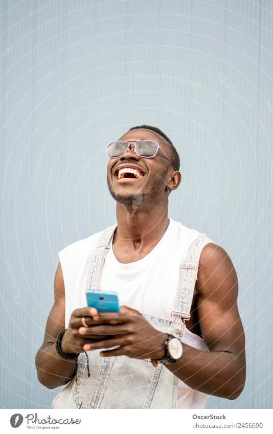 African man blue background with mobile phone. Lifestyle Style Happy To talk Telephone Technology Human being Man Adults Fashion Afro Old To enjoy Listening
