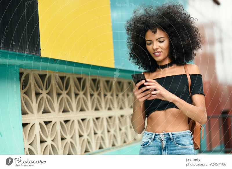Woman with afro hair on the street holding a smart phone Lifestyle Style Joy Happy Beautiful Hair and hairstyles Telephone PDA Technology Human being Feminine