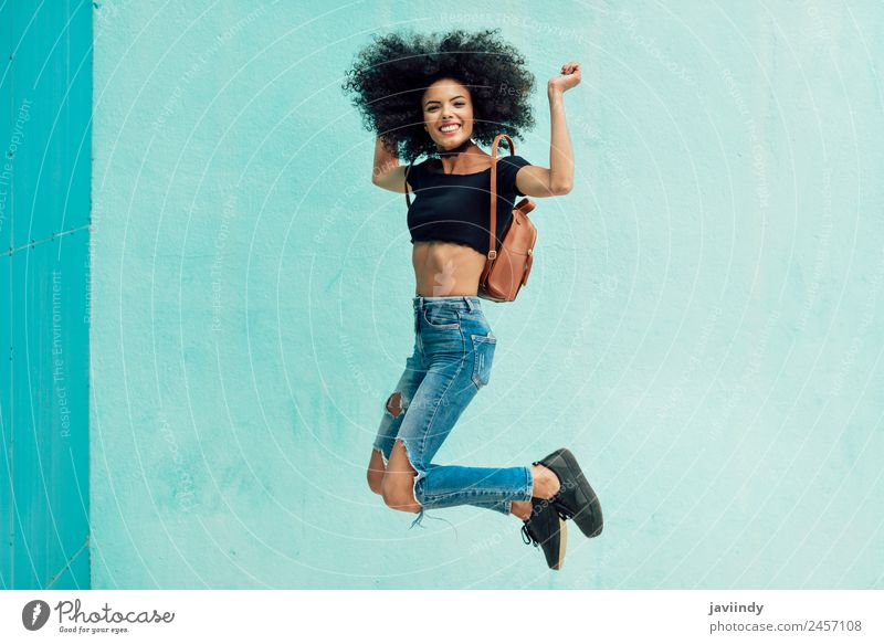 Young mixed woman with afro hair jumping outdoors. Lifestyle Style Happy Hair and hairstyles Face Human being Woman Adults 1 18 - 30 years Youth (Young adults)