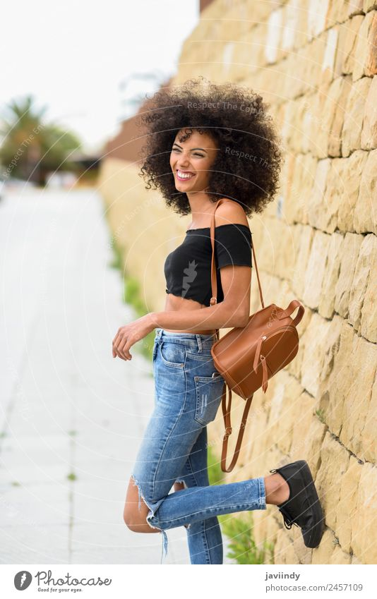 Happy mixed woman with afro hair standing outdoors. Woman Human being Youth (Young adults) Young woman Beautiful Joy 18 - 30 years Black Face Street Adults