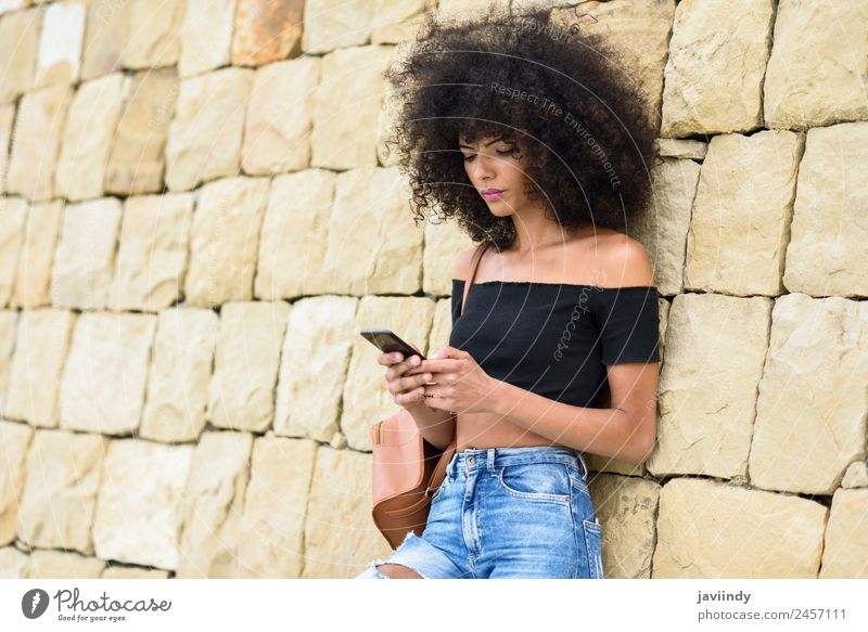 Woman with afro hair looking at her smart phone outdoors Lifestyle Style Beautiful Hair and hairstyles Telephone PDA Technology Human being Young woman