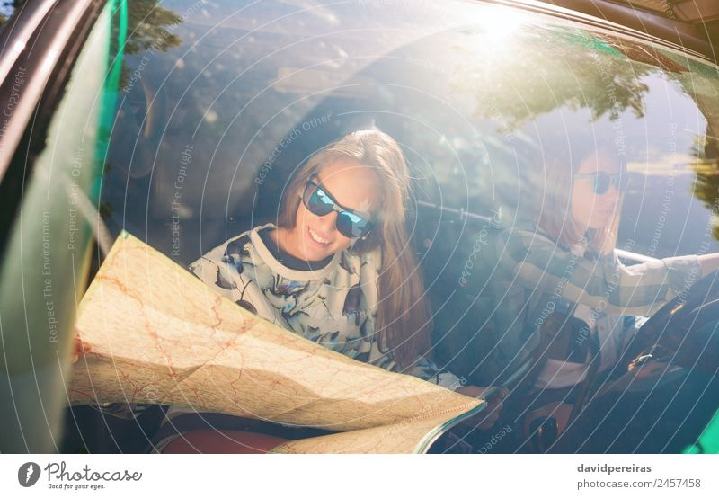 Happy young woman looking a map inside of car Lifestyle Joy Beautiful Leisure and hobbies Vacation & Travel Trip Human being Woman Adults Friendship Couple