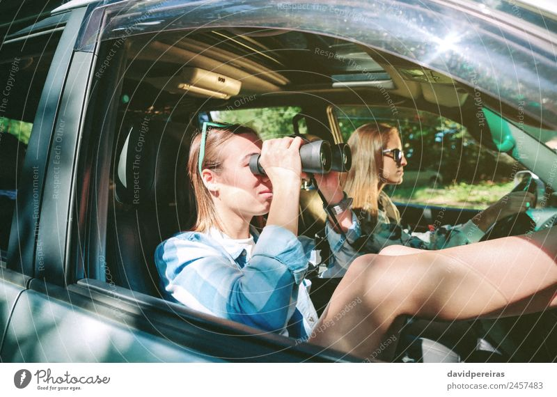 Woman looking through the binoculars and friend driving Lifestyle Happy Beautiful Relaxation Leisure and hobbies Vacation & Travel Trip Human being Adults