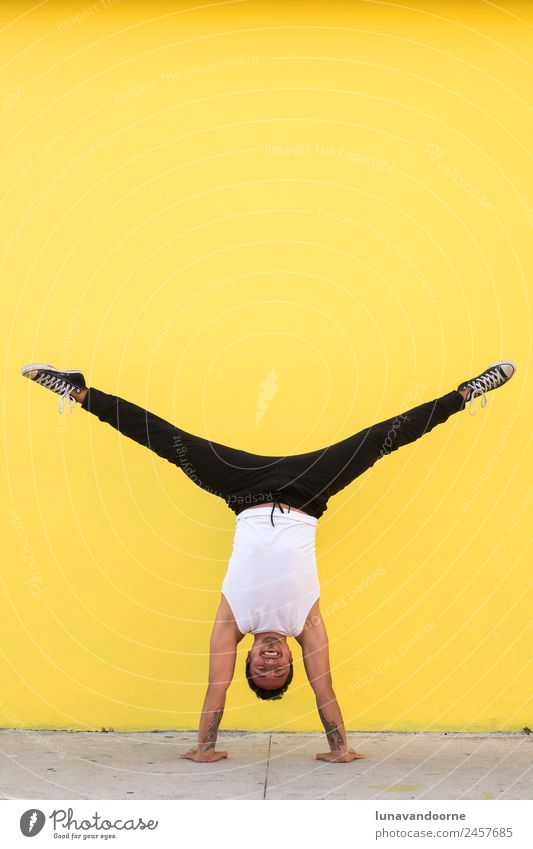 Man practicing yoga, handstand on a yellow wall Lifestyle Joy Athletic Fitness Well-being Sports Sports Training Track and Field Yoga Dance Human being