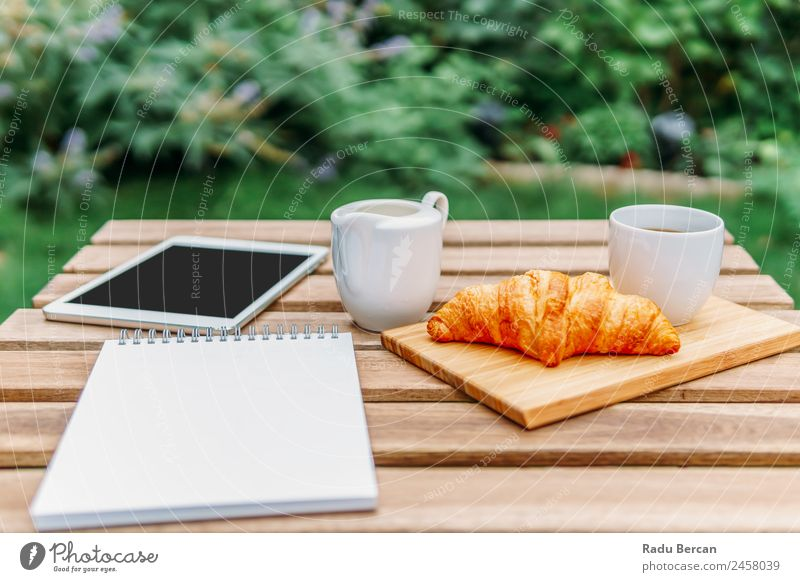Morning Breakfast In Green Garden With French Croissant, Coffee Cup, Orange Juice, Tablet and Notes Book On Wooden Table Background picture Summer White Food