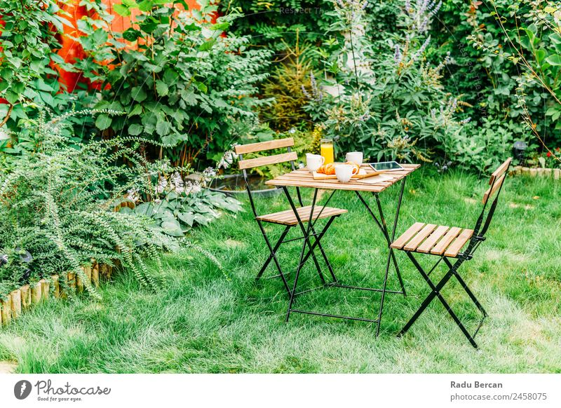 Morning Breakfast In Green Garden With French Croissant, Coffee Cup, Orange Juice, Tablet and Notes Book On Wooden Table Background picture Summer White