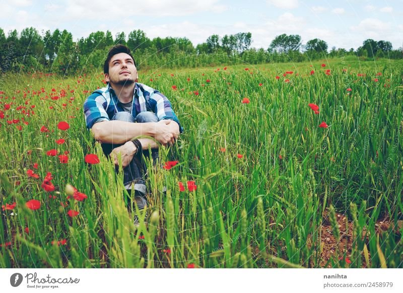 Young man alone in a field of green wheat Human being Nature Youth (Young adults) Man Summer Green Flower Relaxation Far-off places Adults Lifestyle Healthy