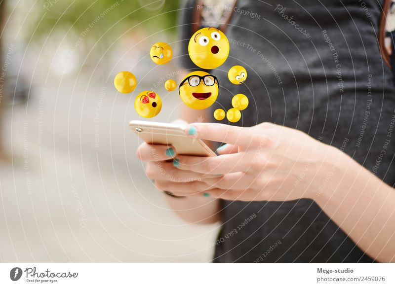 young woman using smartphone sending emojis. Lifestyle Happy Face Telephone PDA Screen Technology Internet Human being Woman Adults Man Hand Funny Modern Smart