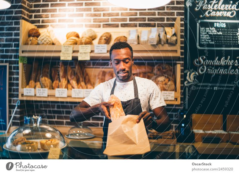 African man works in pastry shop. Bread Blackboard Work and employment Profession Business Human being Man Adults Smiling Stand Sell Happiness Bakery Storage