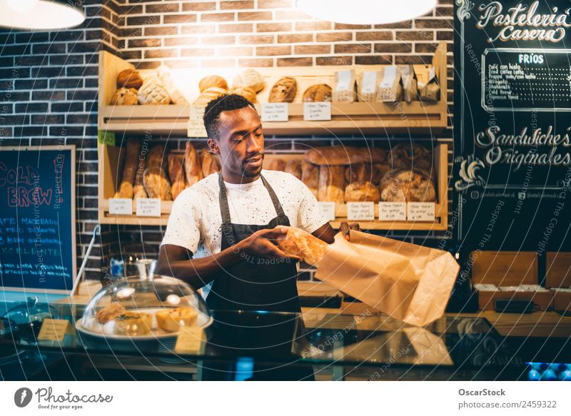 African man works in pastry shop. Human being Man Black Adults Business Copy Space Work and employment Smiling Stand Happiness Profession Bread Blackboard