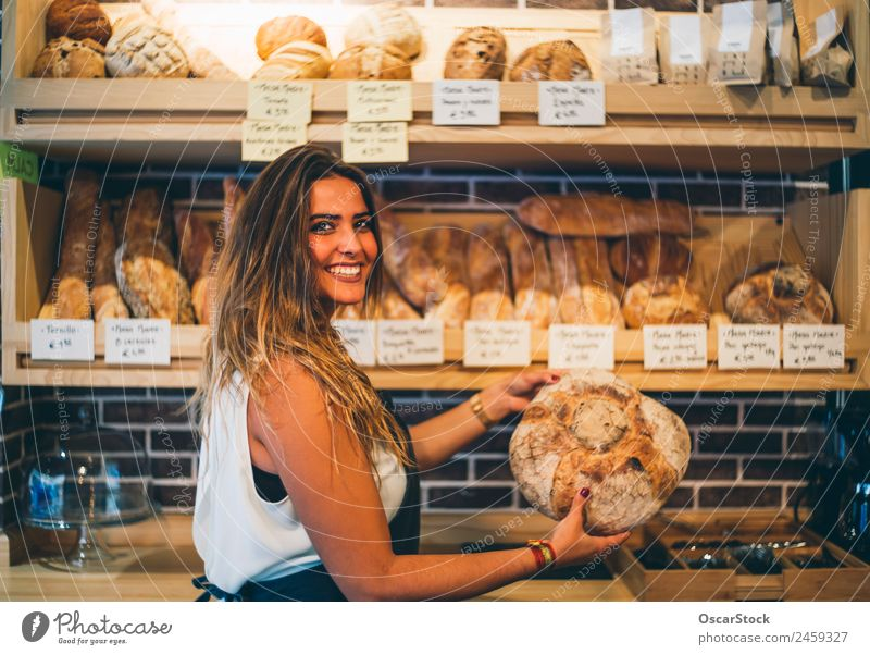 Woman sells in bakery. Bread Shopping Profession Business Human being Adults Smiling Sell Fresh Small Arrangement Retail sector Bread basket Hold Indulgence