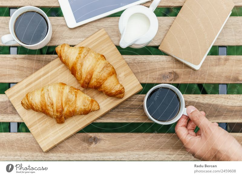 Morning Breakfast In Green Garden With French Croissant, Coffee Cup, Orange Juice, Tablet and Notes Book On Wooden Table Background picture White Food