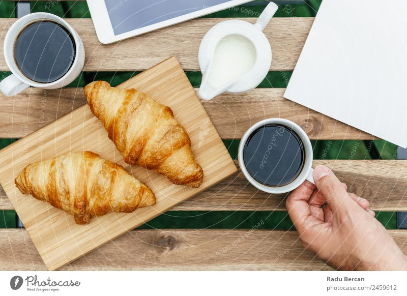 Morning Breakfast In Green Garden With French Croissant, Coffee Cup, Orange Juice, Tablet and Notes Book On Wooden Table Background picture White Food Drinking
