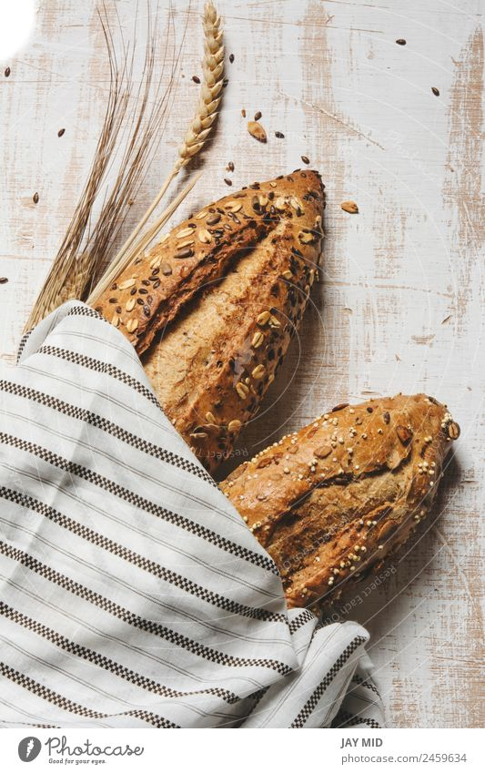 rustic seeded bread, wrapped in striped fabric Food Bread Breakfast Organic produce Diet Group Fresh Brown White Tradition breads loaf of bread corn