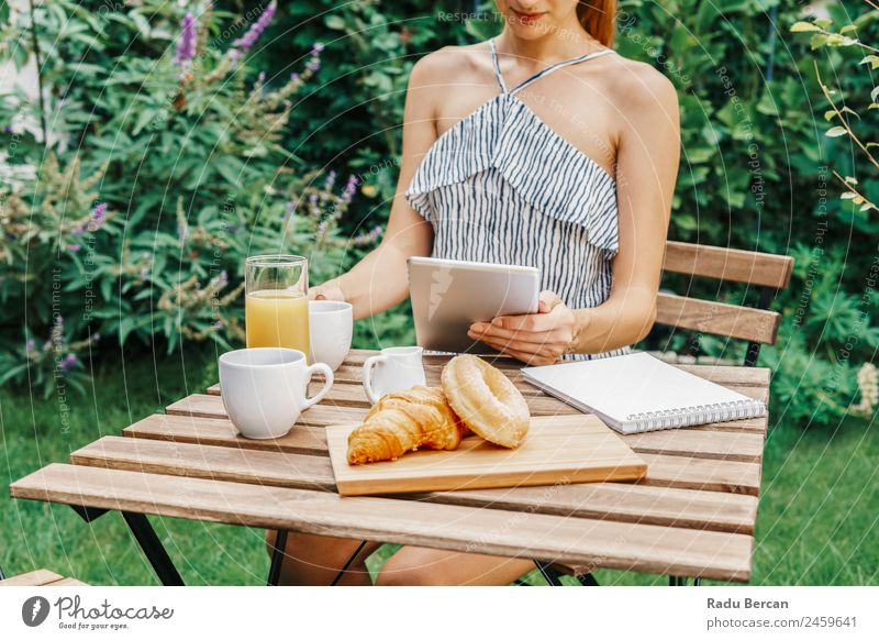 Young And Attractive Woman Having Morning Breakfast In Green Garden With French Croissant, Donuts, Coffee Cup, Orange Juice, Tablet and Notes Book On Wooden Table
