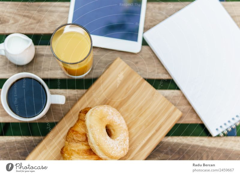 Morning Breakfast In Green Garden With French Croissant, Donuts, Coffee Cup, Orange Juice, Tablet and Notes Book On Wooden Table Background picture White Food