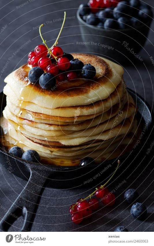Sweet pancakes with currants, blueberries and delicious maple syrup in a cast-iron black pan Pancake Food sugar syrup Redcurrant fruit Dough Baked goods