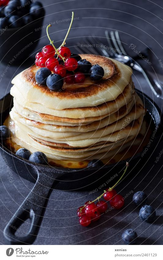 Pancakes with currants and blueberries in a cast iron pan are standing on a dark table Redcurrant fruit Blueberry Cast iron Dough Nutrition Breakfast Buffet