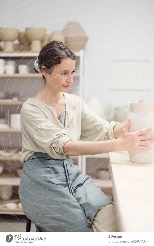 Young female sitting by table and making clay or ceramic mug Crockery Leisure and hobbies Handcrafts Table Work and employment Profession Craftsperson Workplace