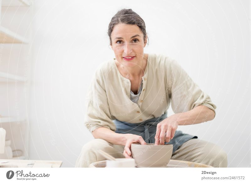 Young female sitting by table and making clay or ceramic mug Crockery Lifestyle Leisure and hobbies Handcrafts Table Work and employment Profession Craftsperson