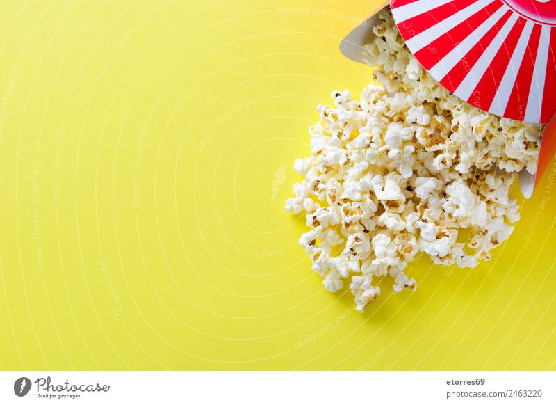 Striped box with popcorn on yellow background. Copyspace Food Nutrition Eating Organic produce Vegetarian diet Fast food Finger food Yellow Red White Popcorn
