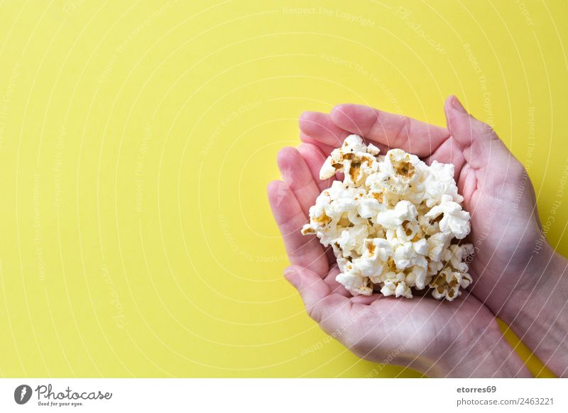 woman with popcorn in hand on yellow background. Copyspace Food Nutrition Eating Organic produce Vegetarian diet Diet Fast food Finger food Catch Yellow White