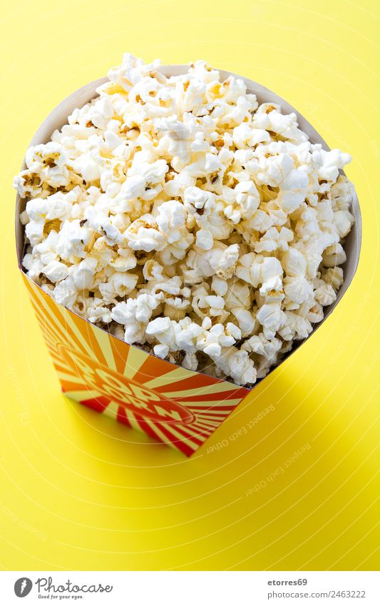 "Striped box with popcorn on yellow background. Food Nutrition Eating Finger food Yellow White ""popcorn cinema salt butter snack delicious maize isolated striped"