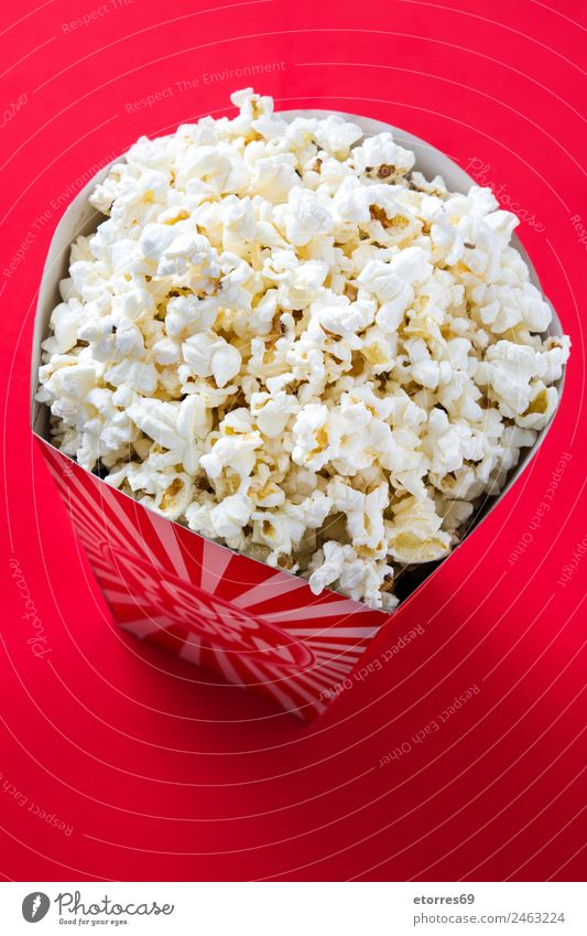 Striped box with popcorn on red background. Food Nutrition Eating Organic produce Finger food Red Popcorn Cinema Salt Butter Snack White Delicious Maize