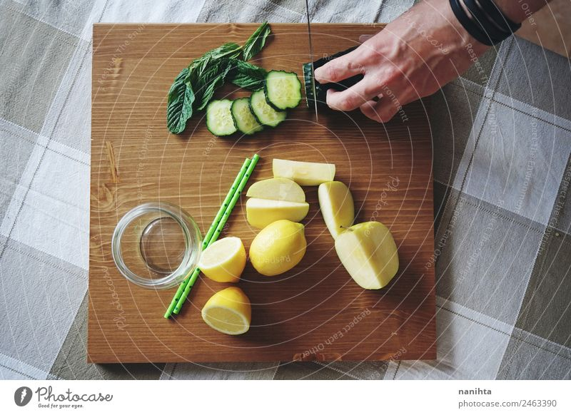 Man cutting fresh vegetables and fruits Food Vegetable Fruit Apple Herbs and spices Cucumber Mint leaf Lemon Slices of cucumber Nutrition Breakfast