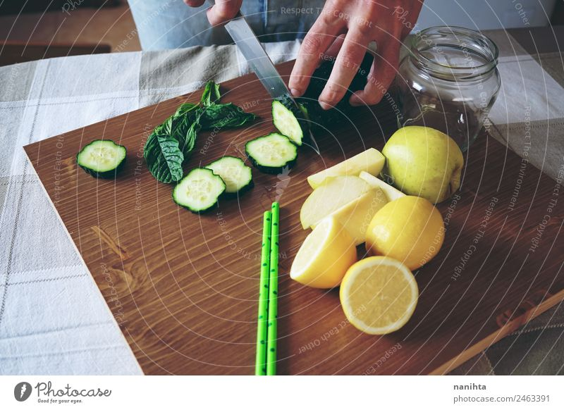 Young man making a smoothie with vegetables Food Fruit Apple Lemon Cucumber Mint Nutrition Eating Organic produce Vegetarian diet Diet Glass Straw Knives
