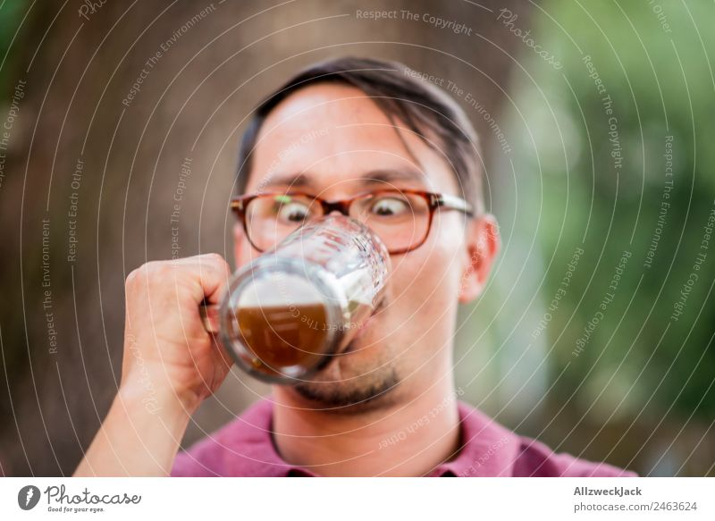 Portrait of a young man with a beer glass in his hand Portrait photograph 1 Person Young man Upper body Looking Inattentive drinking contest Beer glass Beer mug