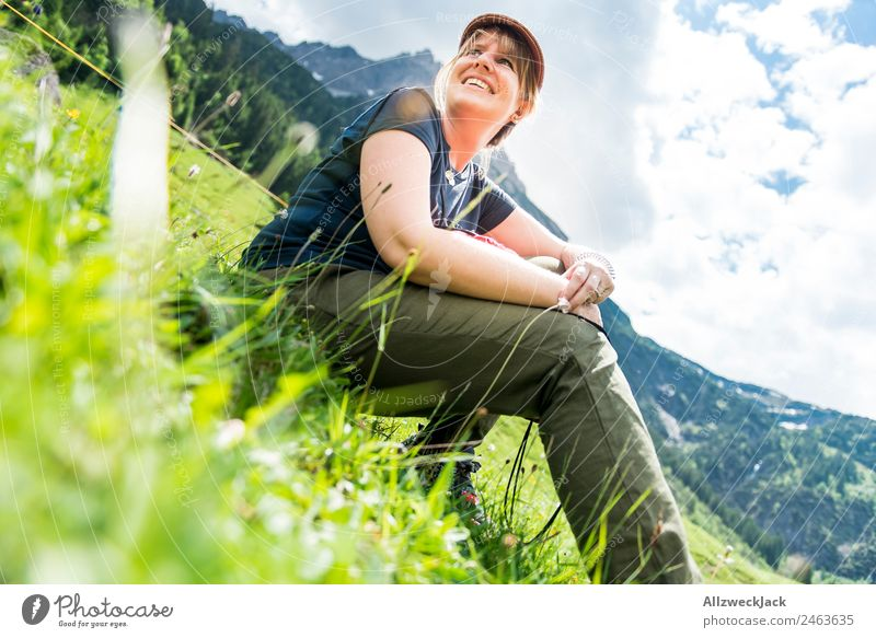 young woman sitting in the grass in front of a mountain panorama Day Beautiful weather Clouds Nature Green Tree Forest Mountain Idyll Vacation & Travel