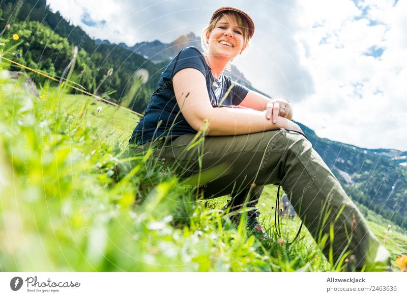 young woman sitting in the grass with mountains in the background Day Beautiful weather Clouds Nature Green Tree Forest Mountain Idyll Vacation & Travel