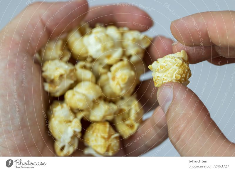 PopCorn Grain Candy Hand Fingers Eating To hold on Popcorn Entertainment Unhealthy Cinema Snack Colour photo Interior shot Studio shot Close-up
