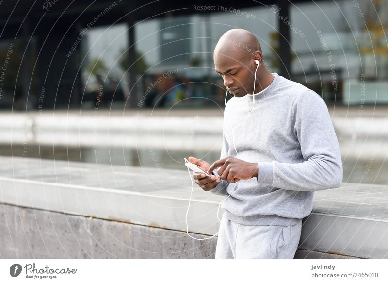 Attractive black man listening to music with earphones Lifestyle Happy Music Sports Telephone PDA Technology Human being Masculine Young man