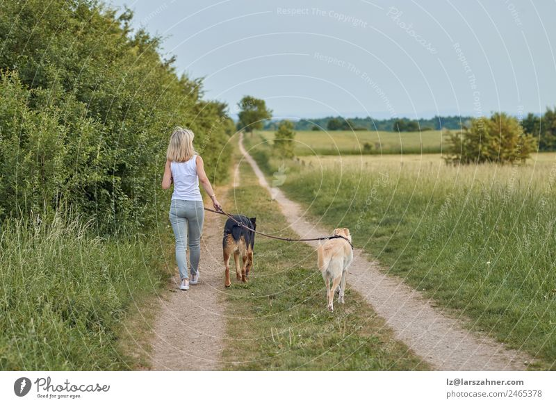 Young blond woman walking her two dogs Lifestyle Happy Beautiful Summer Woman Adults Friendship 1 Human being Nature Animal Warmth Grass Park Blonde Pet Dog