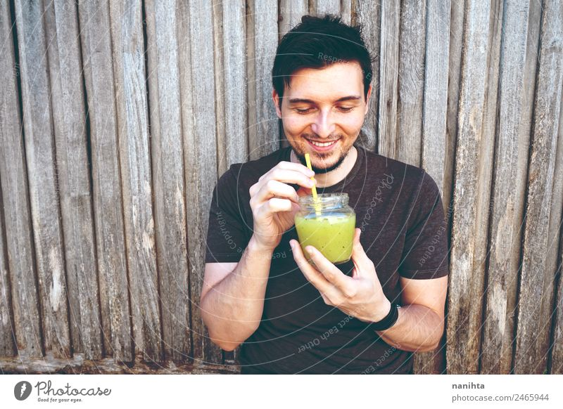 Young happy man enjoying a green smoothie Organic produce Vegetarian diet Beverage Drinking Cold drink Lemonade Juice Milkshake Lifestyle Style Joy Healthy