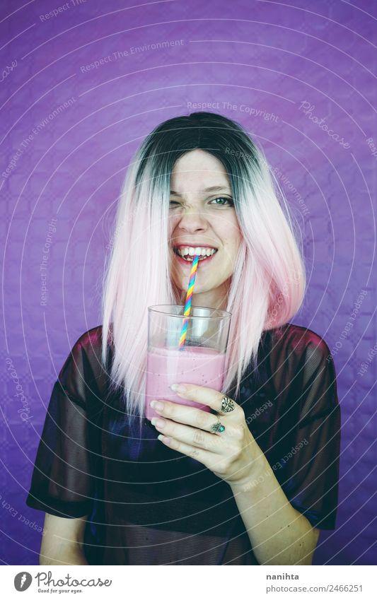 Young happy woman drinking a milkshake Fruit Nutrition Beverage Drinking Cold drink Juice Milk Milkshake Lifestyle Style Joy Hair and hairstyles Healthy Eating