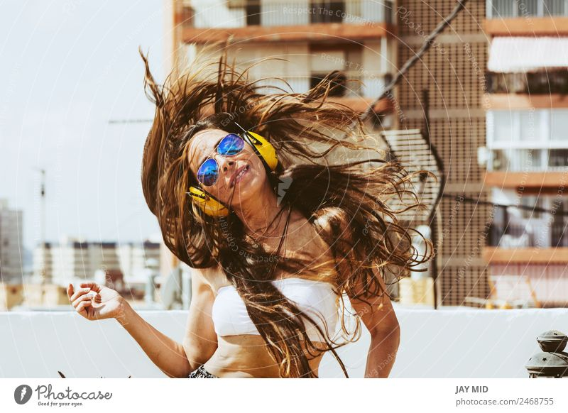 cheerful woman with long hairand and headphones, dances Woman Human being Summer Beautiful Joy Adults Lifestyle Yellow Style Happy Freedom Fashion Jump Modern