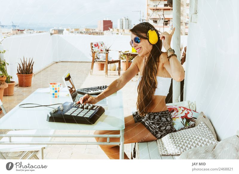 woman sitting with mixing table, in the terrace Lifestyle Joy Summer Table Music Disc jockey Headset PDA Computer Keyboard Technology Feminine Woman Adults Hand