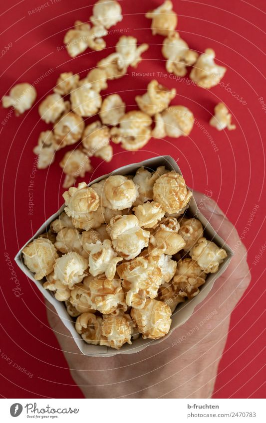 Popcorn in a bag Candy Feasts & Celebrations Man Adults Hand Eating To hold on Happiness Paper bag Cinema Maize Sweet Colour photo Interior shot Studio shot