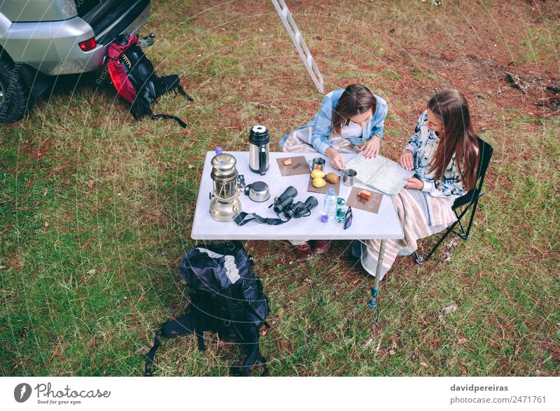 Young women looking road map in campsite - a Royalty Free
