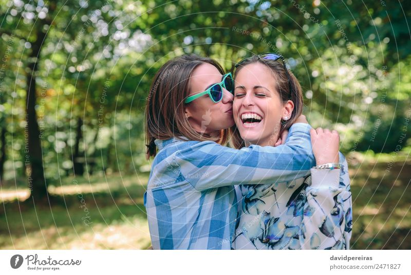 Woman kissing and embracing to female friend laughing Lifestyle Joy Happy Beautiful Leisure and hobbies Summer Human being Adults Friendship Couple