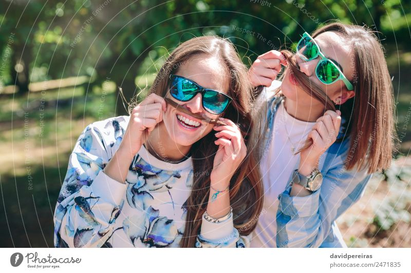 Women doing moustaches with hair and laughing Lifestyle Joy Happy Beautiful Leisure and hobbies Summer Mountain Human being Woman Adults Friendship Couple