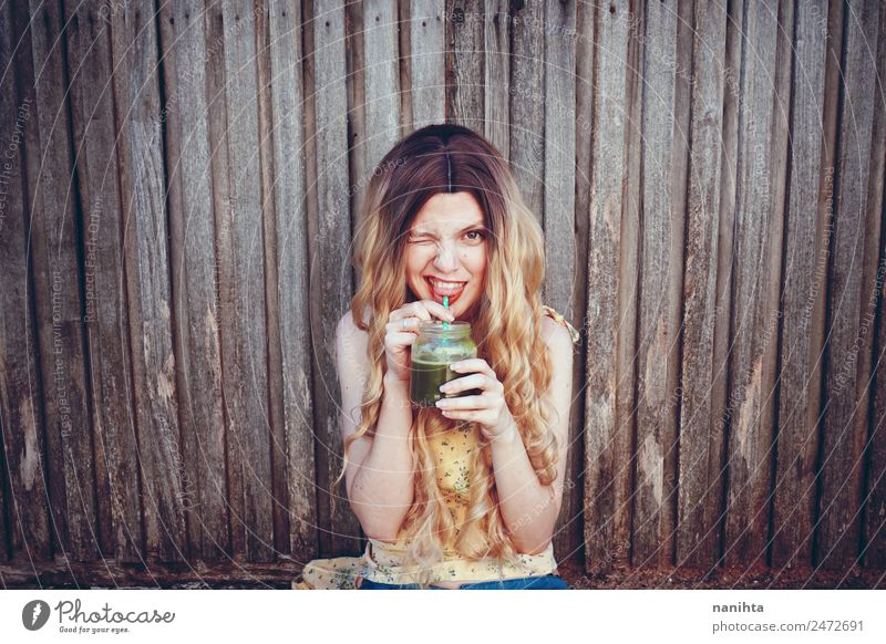 Young happy woman drinking a green smoothie Vegetable Beverage Drinking Cold drink Juice Milkshake Lifestyle Style Joy Beautiful Hair and hairstyles