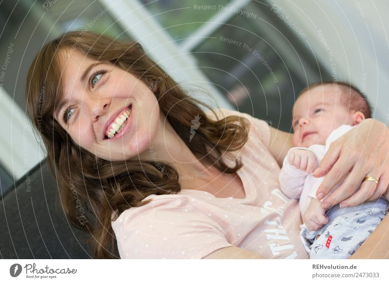 Mother with small baby Lifestyle Harmonious Well-being Flat (apartment) Human being Feminine Baby Adults 2 0 - 12 months 30 - 45 years To hold on Smiling