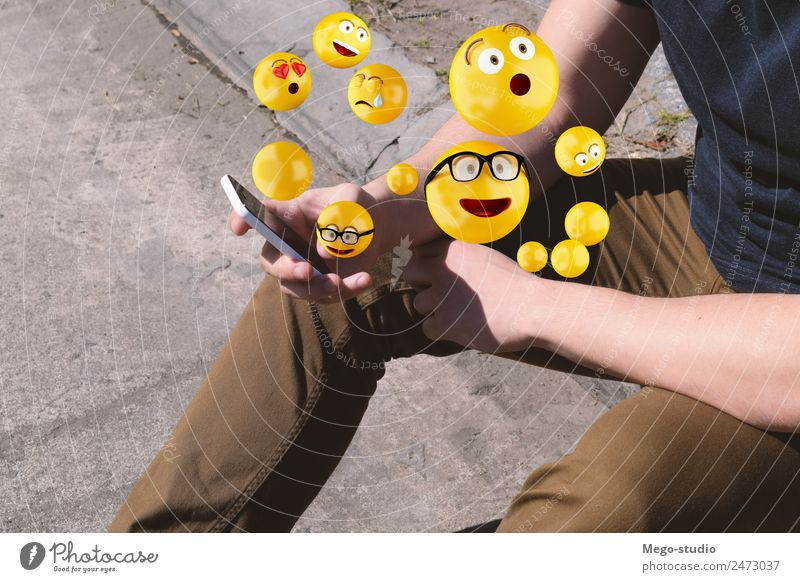 man using smartphone sending emojis. Lifestyle Happy Face Telephone PDA Screen Technology Internet Human being Man Adults Hand Funny Modern Smart Emotions young