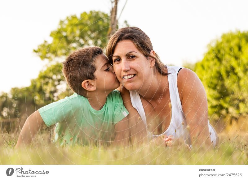 Little boy kissing his mother on a field in summer Woman Child Nature Summer Beautiful Sun Joy Adults Lifestyle Love Family & Relations Grass Happy Boy (child)